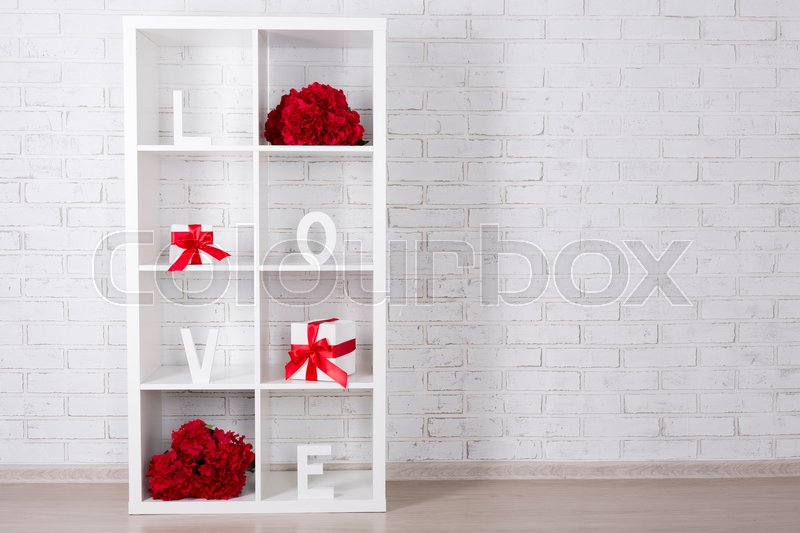 Stock image of 'modern wooden shelf with flowers and gifts over white brick wall background'