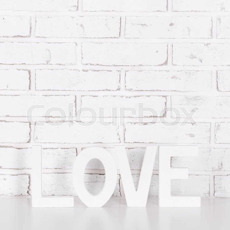 Stock image of 'wooden word love over white brick wall background'