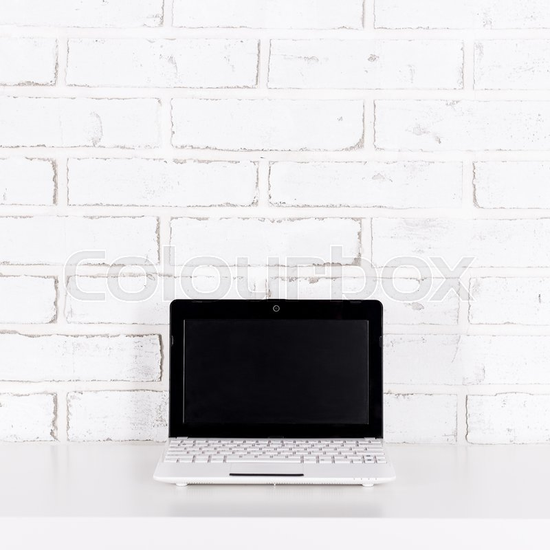 Stock image of 'modern laptop with blank screen on the table over white brick wall background'