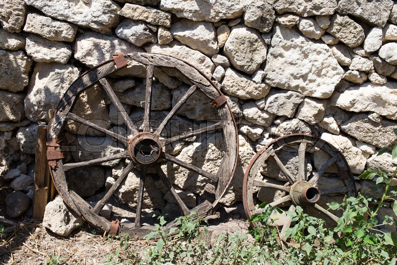 Stock image of 'Old cart wooden wheels neat stone wall as a background.'