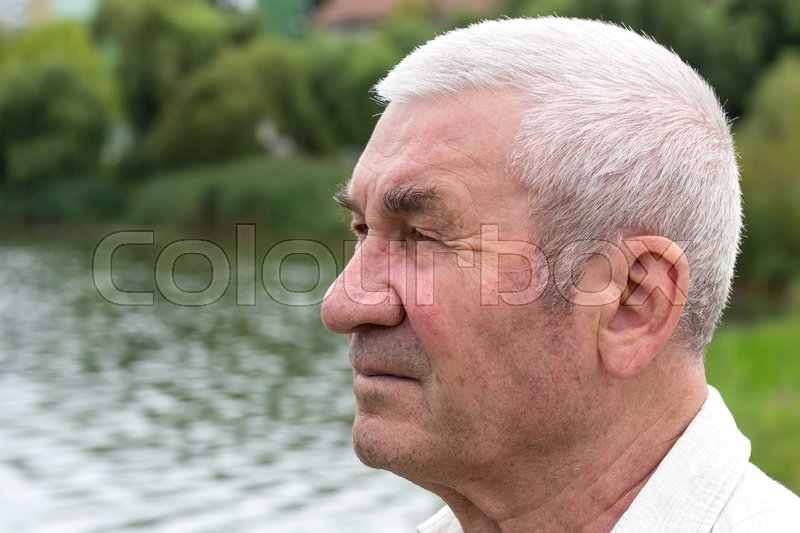 Stock image of 'Portrait of old man closeup against lake water with bokeh as a background.'