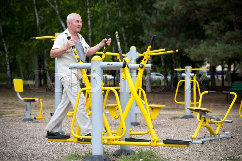 Stock image of 'Old man making exercises on outdoor gym against green summer park as a background.'