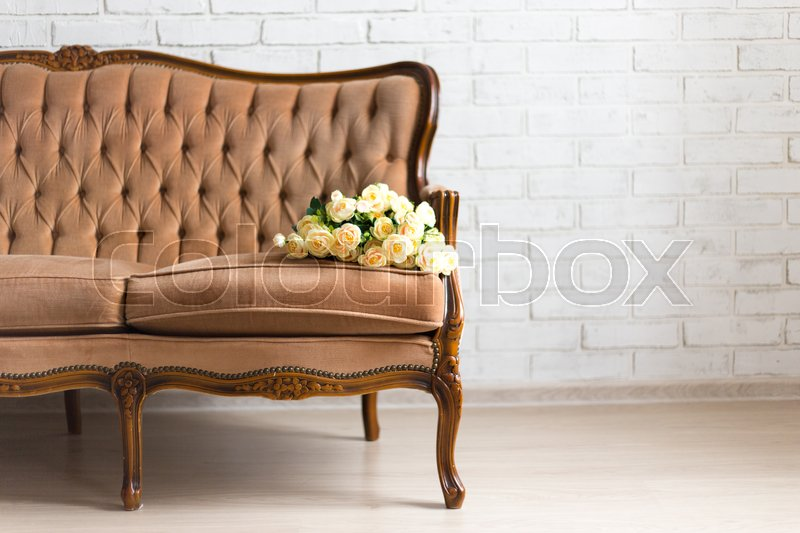 Stock image of 'vintage rococo sofa with flowers over white brick wall'