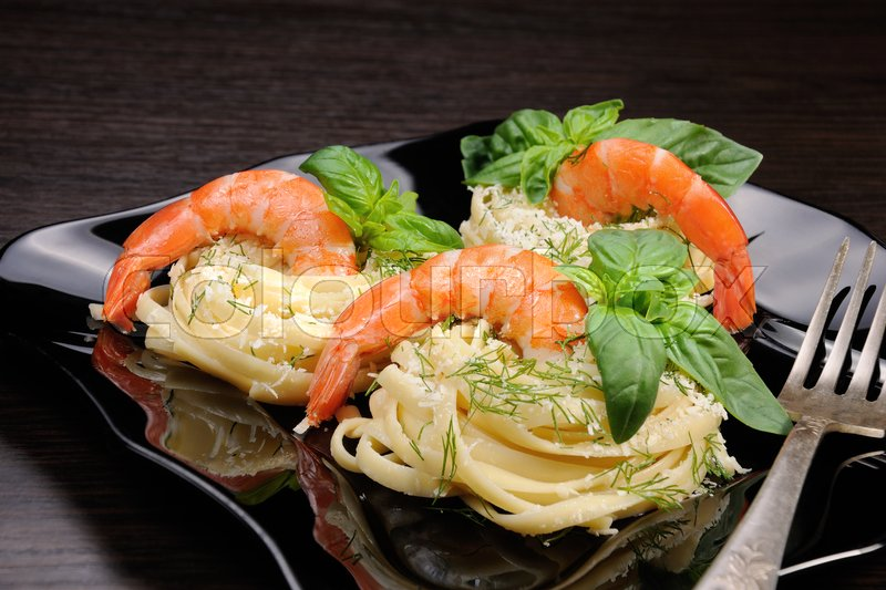 Stock image of 'Nests of spaghetti with parmesan flavored with dill, shrimp and basil.'
