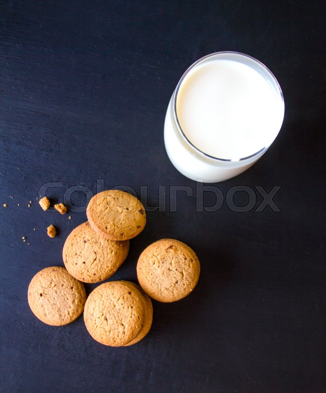 Stock image of 'Oatmeal cookies and milk glass on wood table'