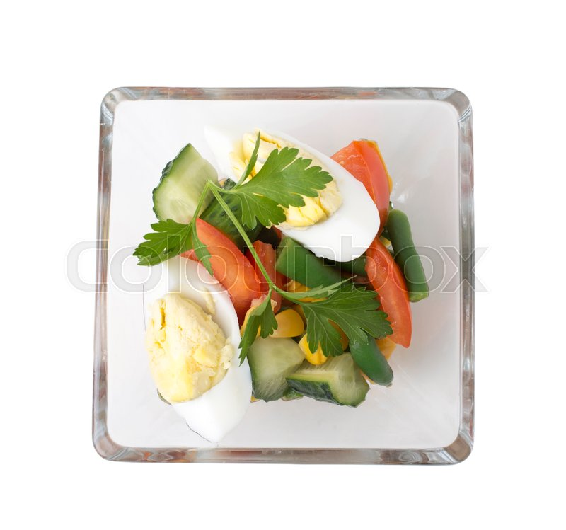 Stock image of 'Closeup of tomatos with cucumbers and eggs in a glass plate. Isolated on a white background.  '