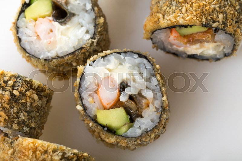 Stock image of 'Crunchy sushi rolls with snow crab and avocado with delicious sauce. Macro. On a table as a background.'
