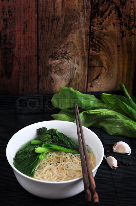 Stock image of 'Noodle bowl with ingredients on wooden background'