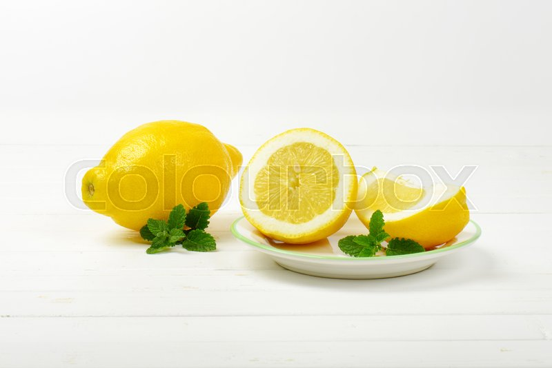 Stock image of 'whole and sliced lemons on white plate and wooden background'