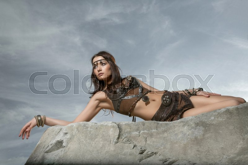 Stock image of 'Young beautiful woman dressed in a leather wear looking like an amazon or warrior lying on a big stone. Dramatic beauty shot '