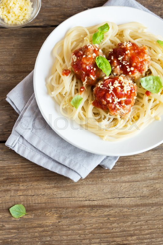 Stock image of 'Spaghetti pasta with meatballs, tomato sauce, grated parmesan cheese and fresh basil - healthy homemade italian pasta on rustic wooden background with copy space'