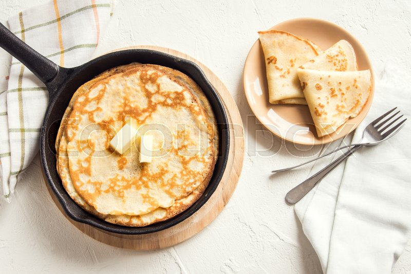 Stock image of 'Homemade crepes with butter in cast iron pan over white background  - cooking fresh homemade breakfast crepes pancakes food'