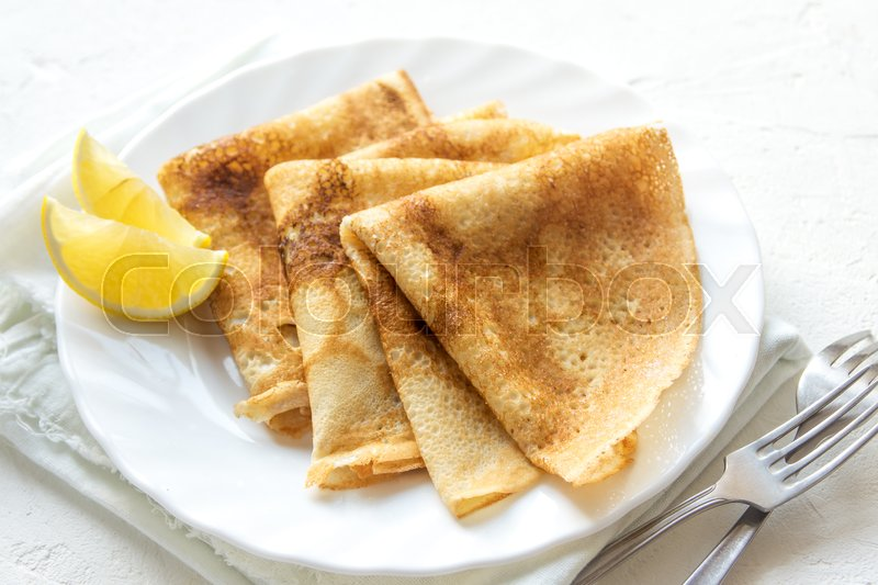 Stock image of 'Crepes Suzette with lemon on white plate over white background, copy space. Delicious homemade Crepes for breakfast.'