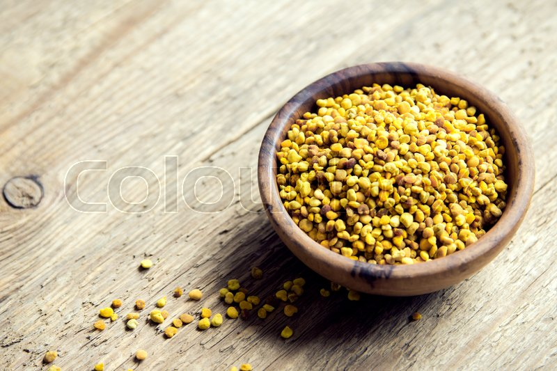 Stock image of 'Bee pollen in bowl over wooden background. Healthy organic raw diet vegetarian food ingredient - bee pollen.'