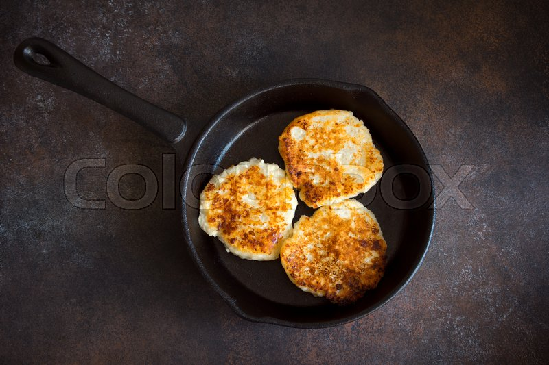 Stock image of 'Rustic homemade curd pancakes in cast iron pan for breakfast, country style. Healthy rustic food, cottage cheese pancakes.'