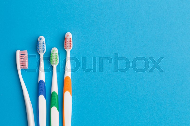 Stock image of 'Colorful toothbrushes on blue background, space for text'