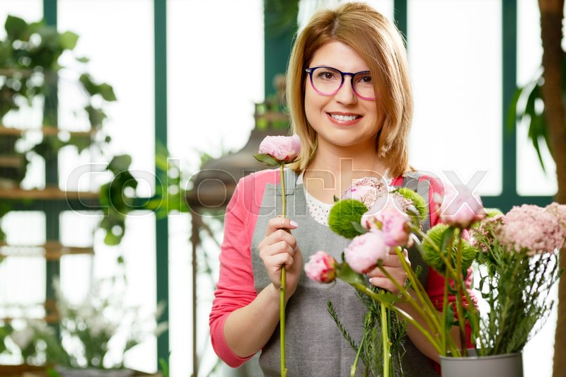 Stock image of 'Young model florist in glasses with flowers at store'