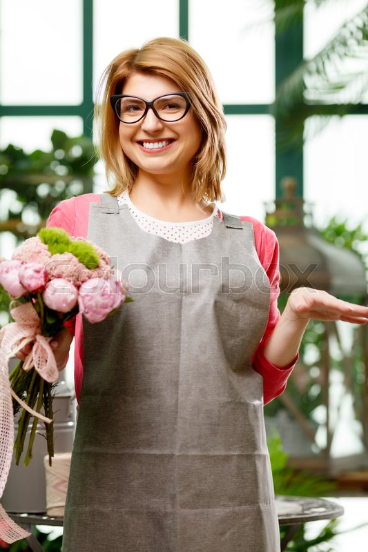 Stock image of 'Young smiling woman in greenhouse among green flowers'