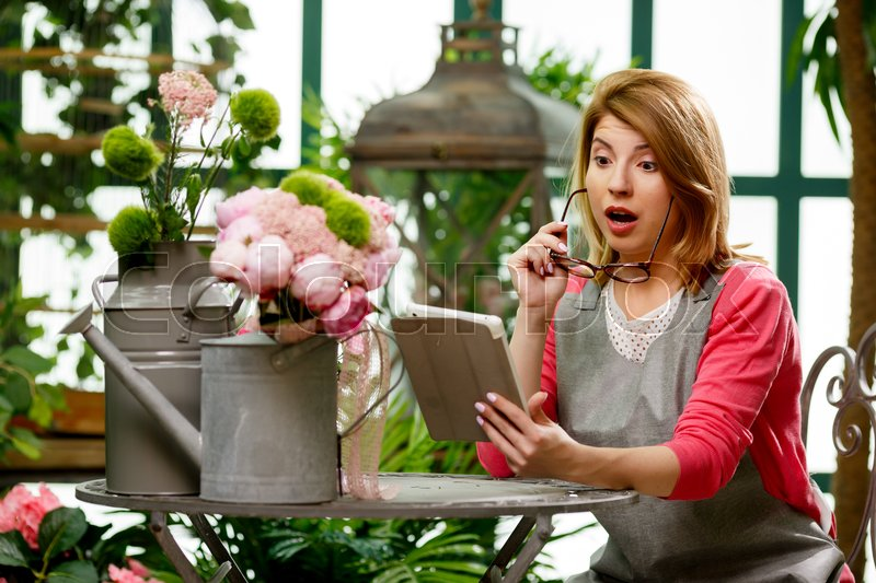 Stock image of 'Woman with tablet at table with flowers in store'