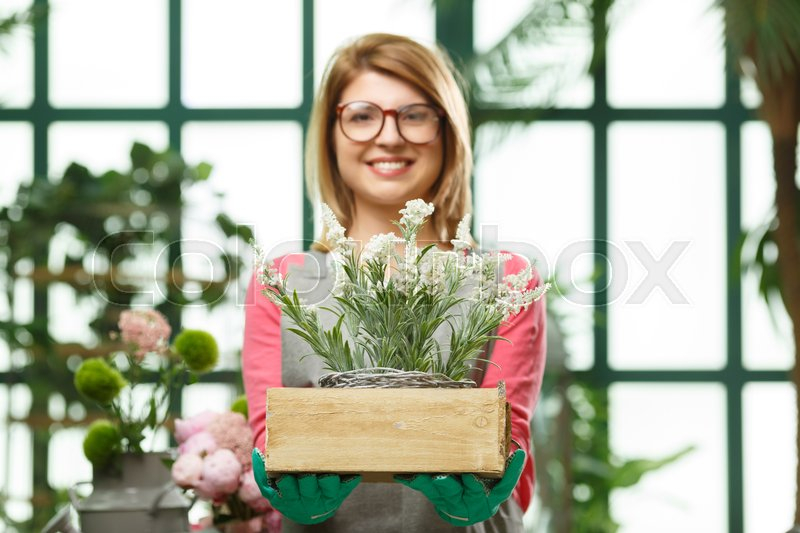 Stock image of 'Happy girl with flower box in store. Focused on flowers.'