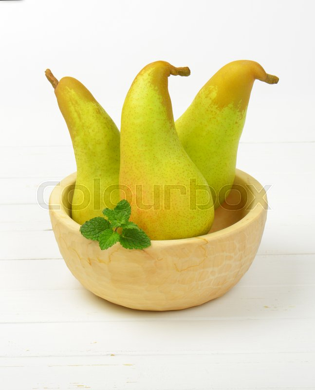 Stock image of 'three yellow pears in wooden bowl'