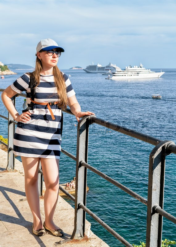 Stock image of 'Young woman at Adriatic Sea waterfront in Dubrovnik, Croatia'