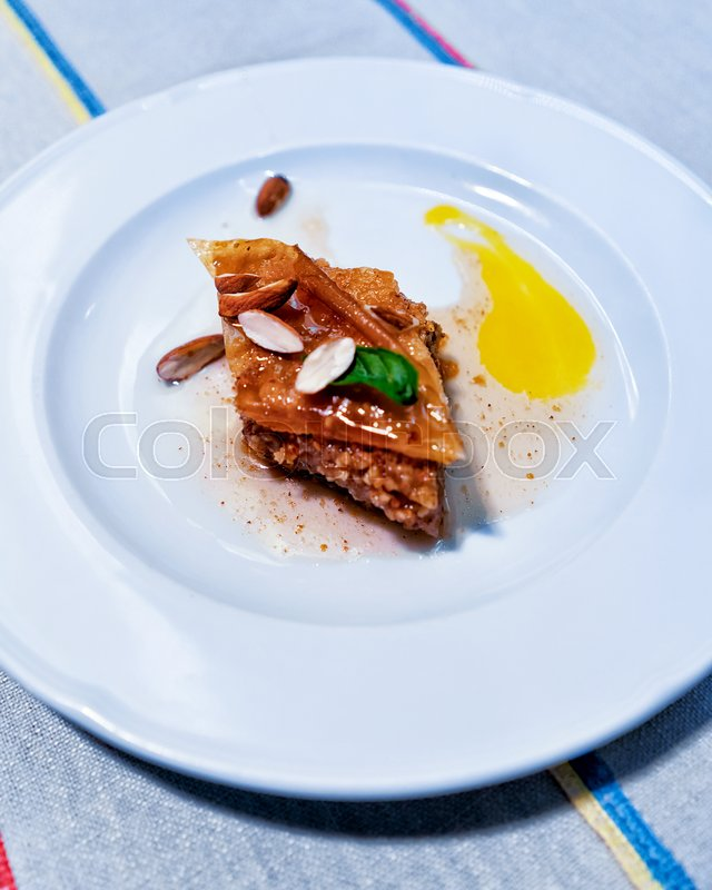 Stock image of 'Turkish baklava dessert on the white plate in a restaurant'