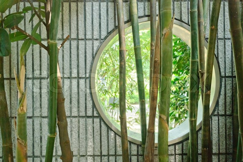 Round Chinese Window In Wall In Garden With Bamboo Stock