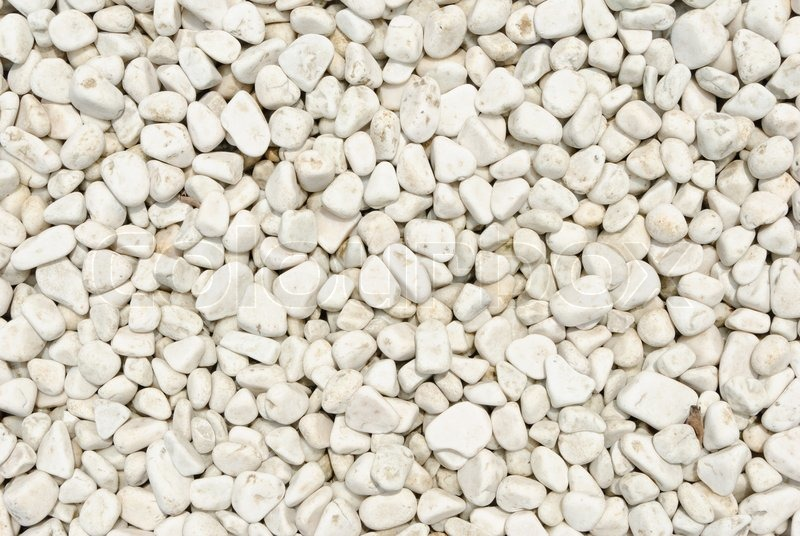Small naturally polished white rock pebbles background, stock photo
