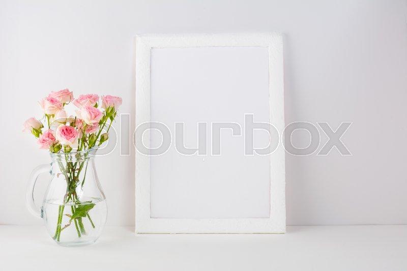 Frame mockup with pink roses. Frame mockup. White frame mockup. Poster Mockup. Styled mockup. Product mockup. Design Mockup. Empty frame mockup. Portrait frame mockup, stock photo