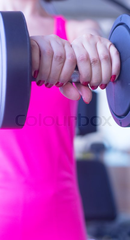 Stock image of 'Woman working out female exercise fitness sports weights training in gym health studio.'