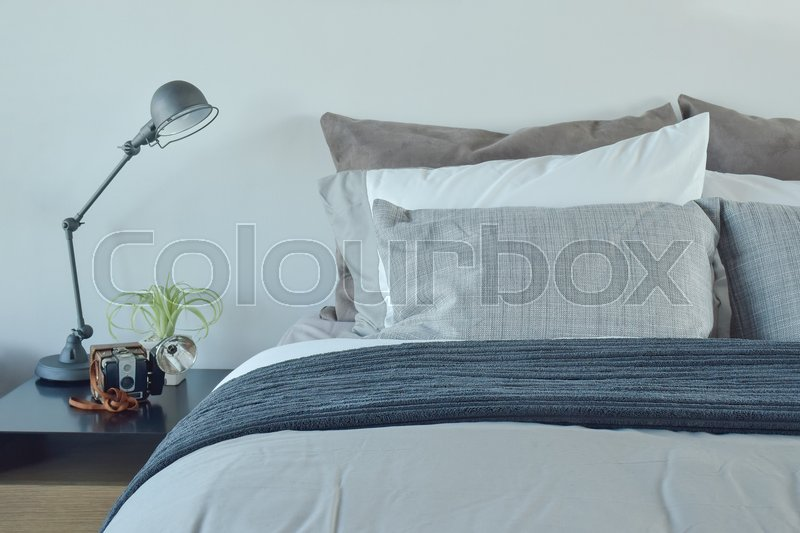 Blue and gray color scheme bedding with industrial style table lamp, stock photo