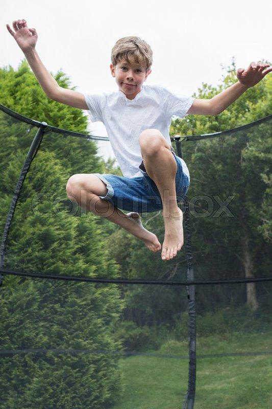 Mid Air Shot Of Boy On Trampoline In Garden, stock photo