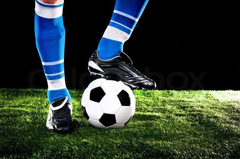 Soccer ball with his feet on the football field | Stock Photo ...