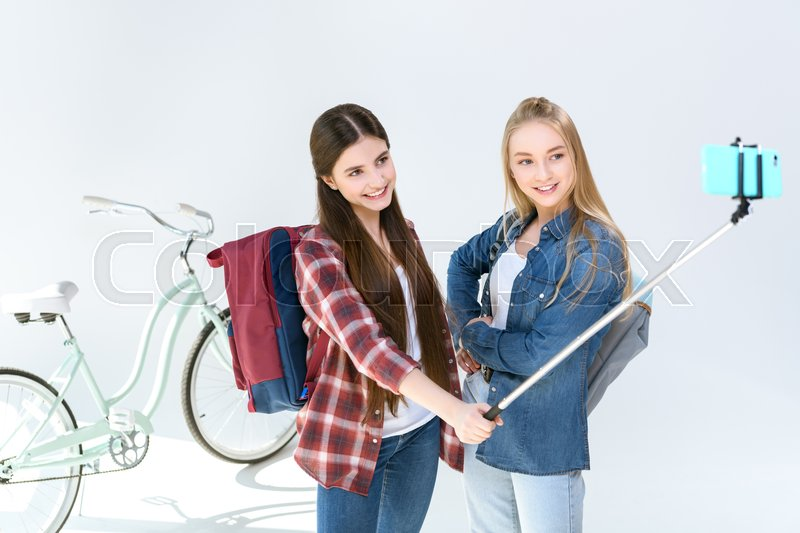 Portrait of teenage girls in casual clothing taking selfie on smartphone together isolated on white, stock photo