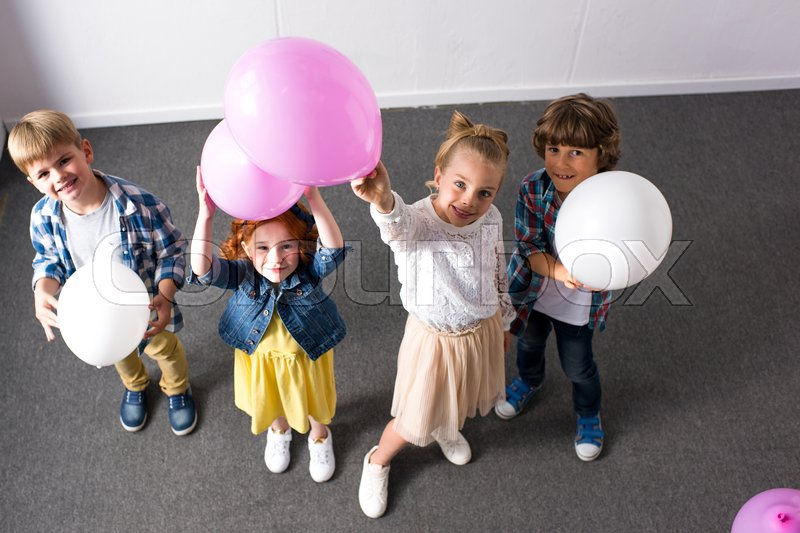 High angle view of cute happy children holding balloons and smiling at camera at birthday party, stock photo