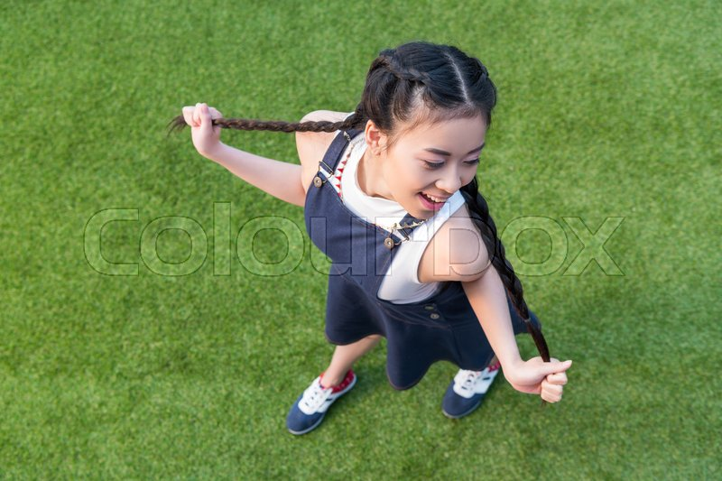 High angle view of beautiful smiling asian girl posing while standing on green grass, stock photo