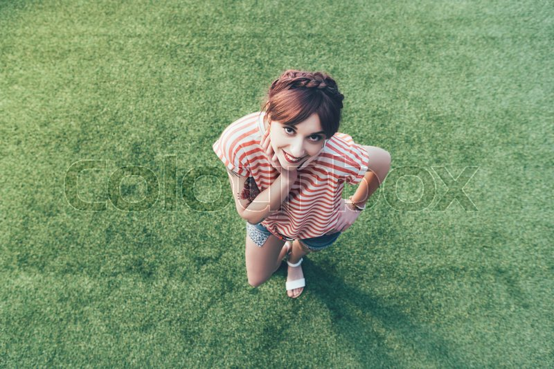 High angle view of beautiful happy girl smiling at camera while standing on green grass, stock photo