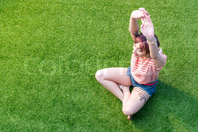 High angle view of smiling young woman stretching hands while sitting on green grass, stock photo