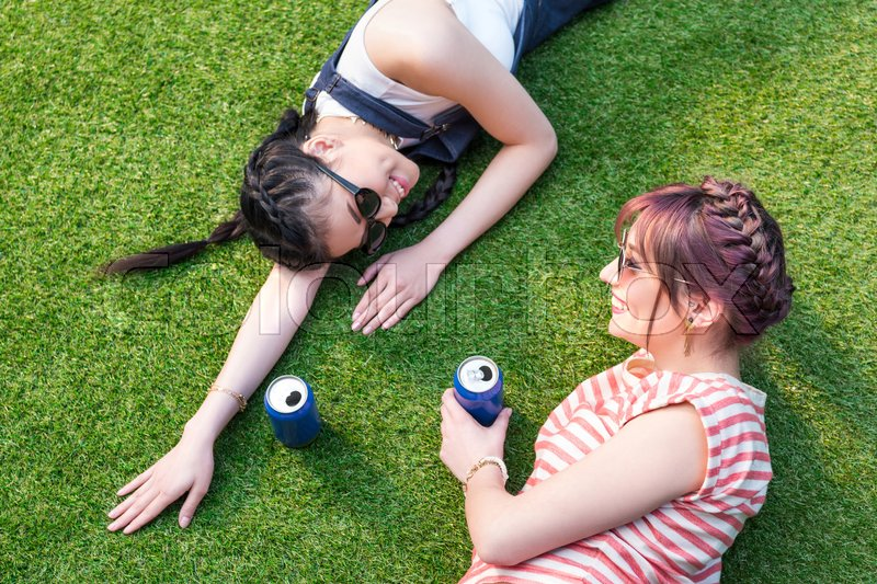 High angle view of multiethnic girls with soda cans smiling each other while lying on lawn, stock photo