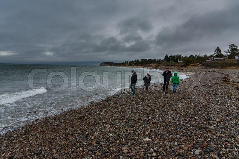 En familie går tur på stranden på en ... | Stock foto | Colourbox