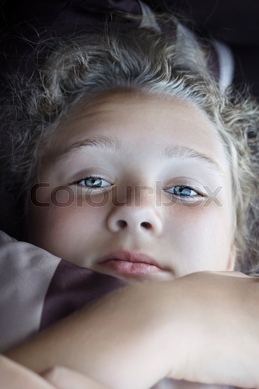 Beautiful girl is hiding her face by striped pillow, stock photo