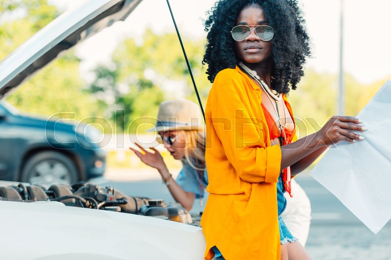 African american woman looking for destination on map while friend checking broken car, stock photo
