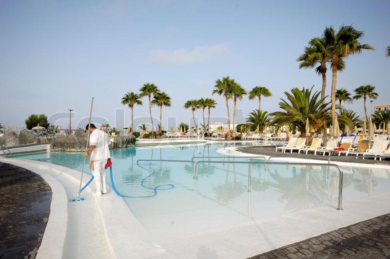 A Man Is Cleaning The Pool At A Nice Hotel Resort Stock Photo Colourbox