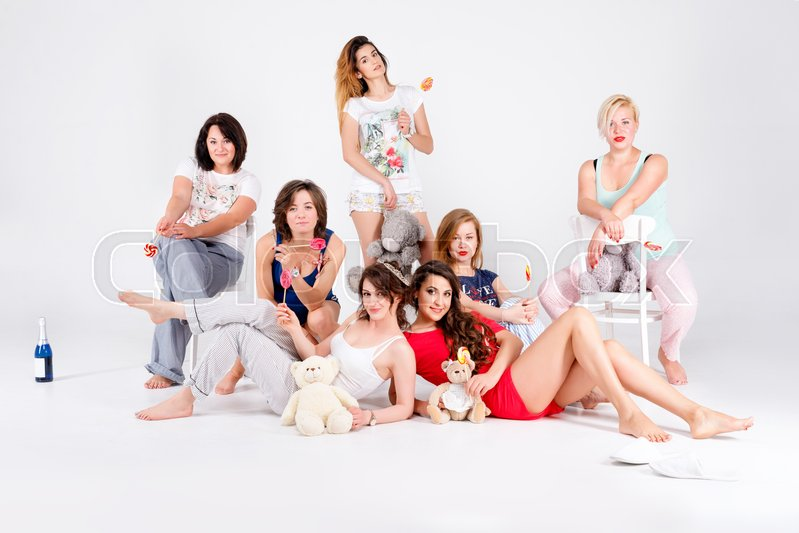 Girls in pajamas posing in studio. Happy female friends making pajama party. Women day, celebration, friends, bachelorette party, friendship, birthday and holidays concept, stock photo