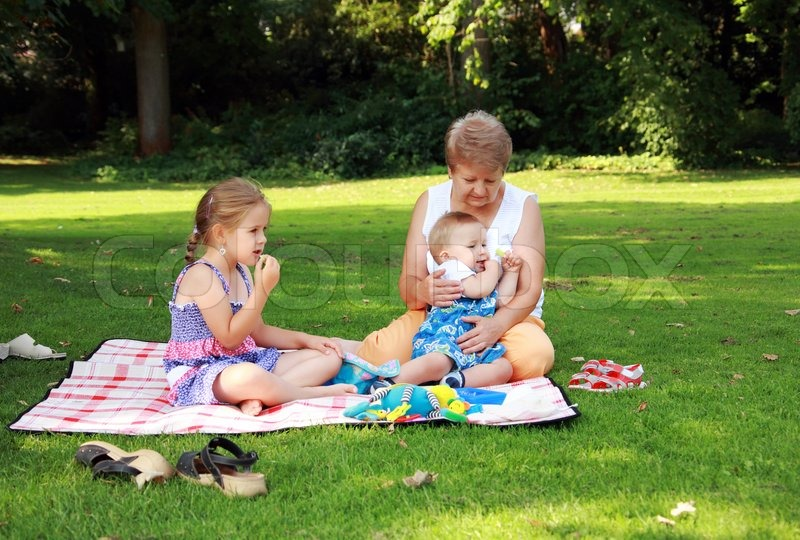 Kids have a small picnic with grandma, stock photo