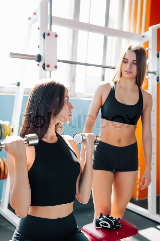 Cute Sporty young woman doing exercise in a fitness center with her personal coach. She is working exercises to strengthen her chest, stock photo