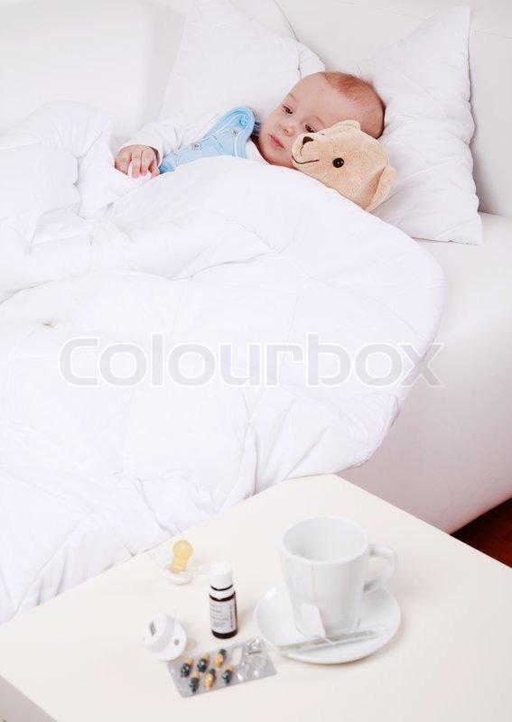 baby und teddyb r im bett liegend mit tasse tee und medizin stockfoto colourbox. Black Bedroom Furniture Sets. Home Design Ideas