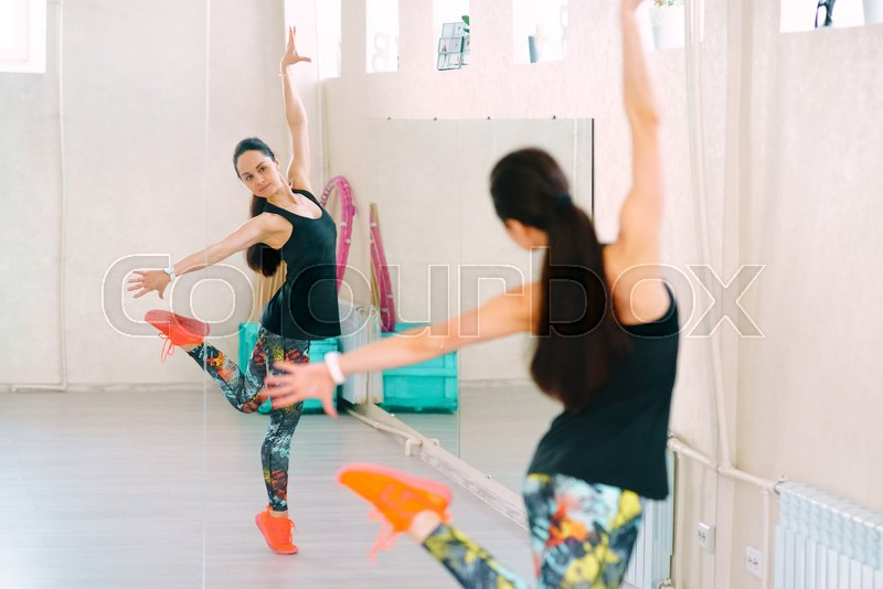 Young sporty women training in dance hall, stock photo