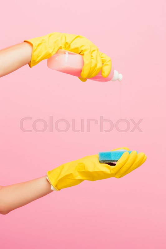 The woman\'s hand cleaning on a pink background. Cleaning or housekeeping concept background. Frame for text or advertising, stock photo